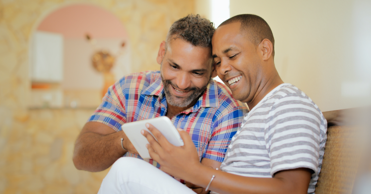 two dads who want to start a family look at available gestational surrogates on an iPad