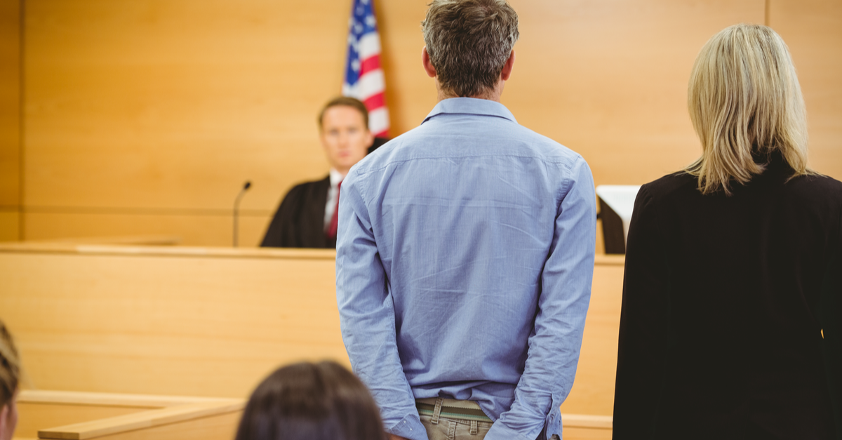 A handcuffed man faces a judge in court