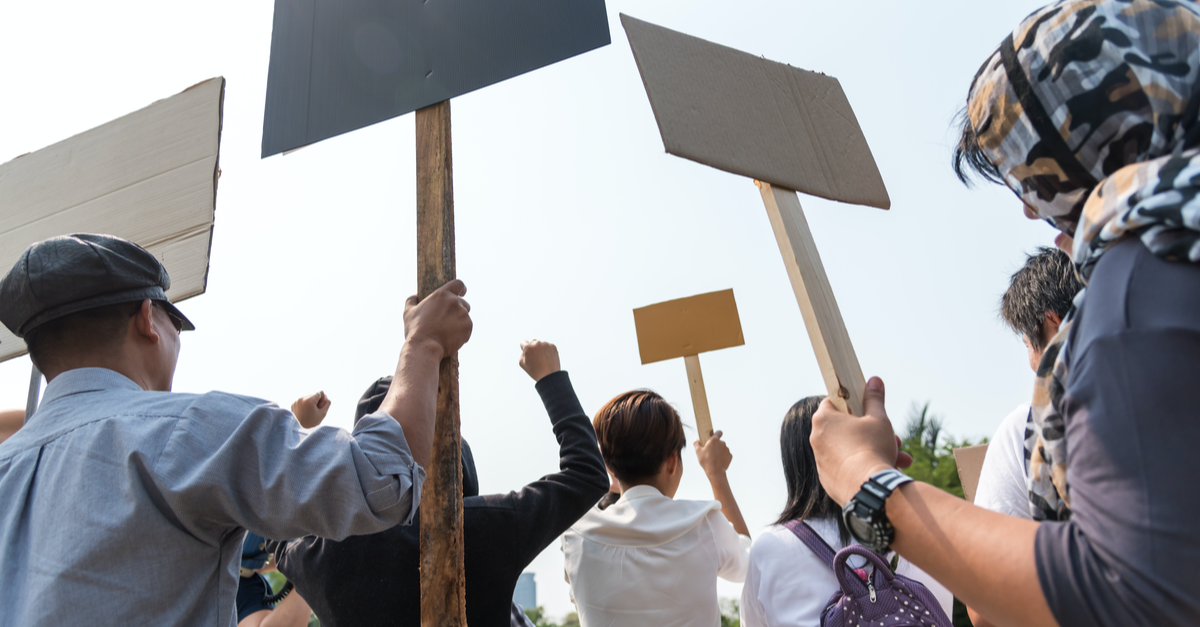 Protesters are seen holding signs