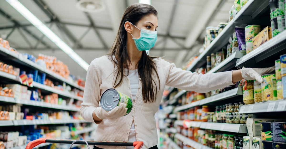 A woman wearing gloves and a mask shops for groceries