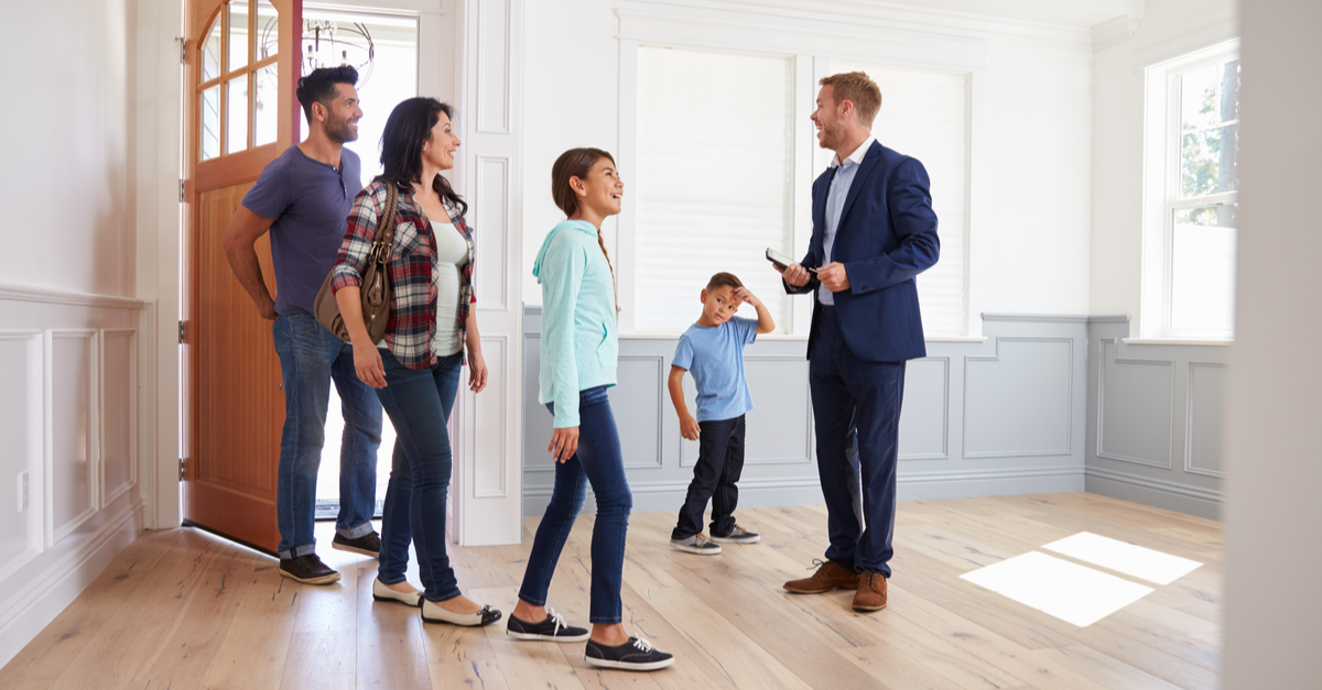 A family is shown a new home by their real estate agent