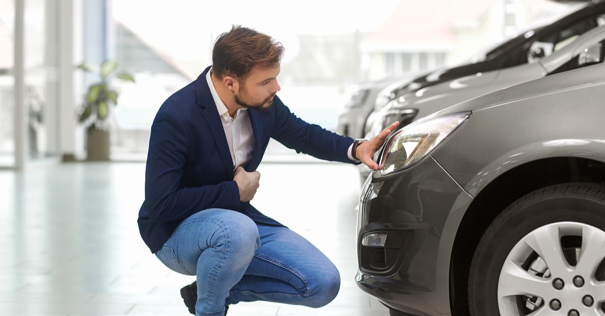 A man examines a new car he considers buying.
