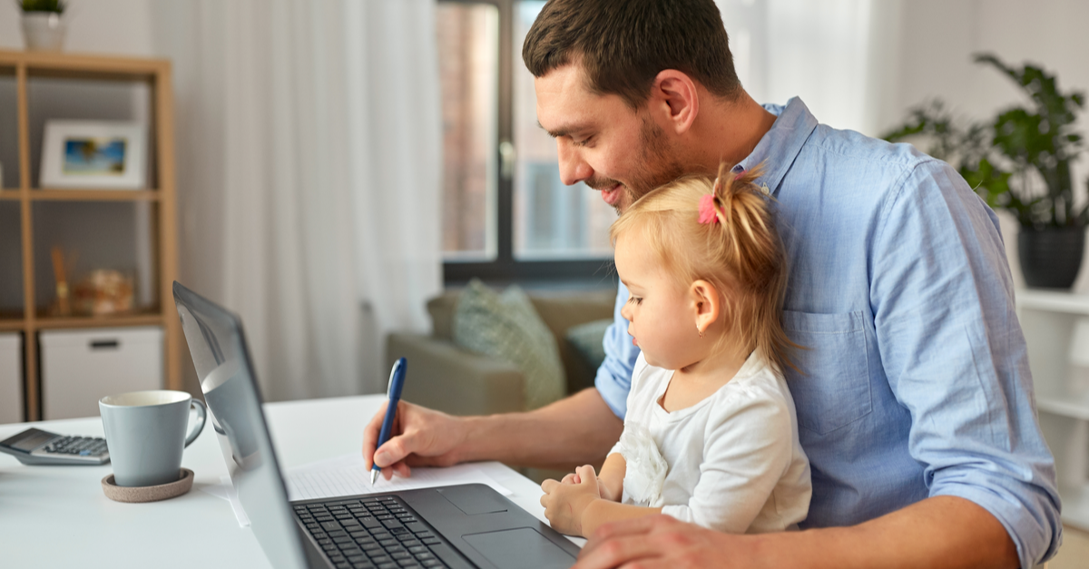 A man does calculations regarding his mortgage forbearance while he holds his toddler daughter in his lap