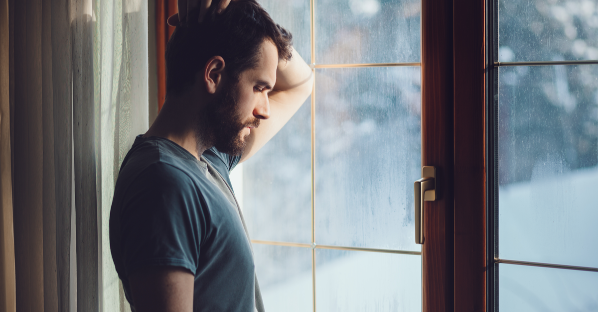A college student looks out the window and considers getting mental health support