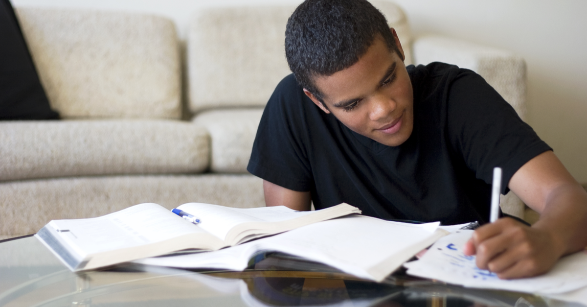 A young male college student does homework in his apartment