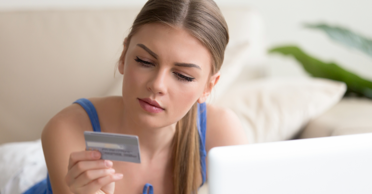 a young woman contemplates an online credit card purchase