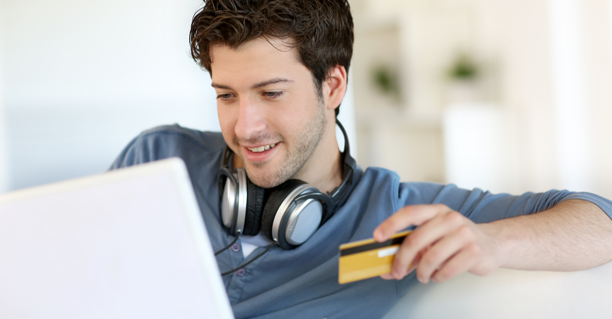 A young male college student orders an item online with a credit card