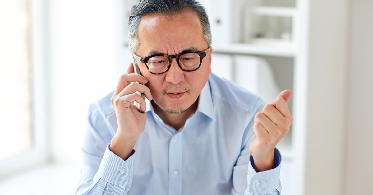 A man is called on the phone regarding giving a donation and shows a skeptical look on his face as the caller asks for personal information.