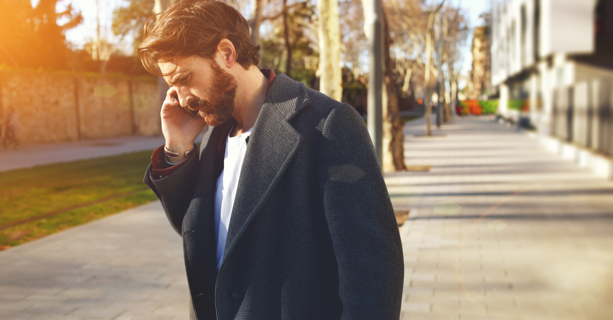 A man stands outside and speaks with his creditor on his cell phone