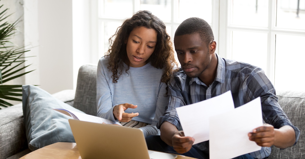 A couple sits in front of a computer looking at paperwork and discussing their finances