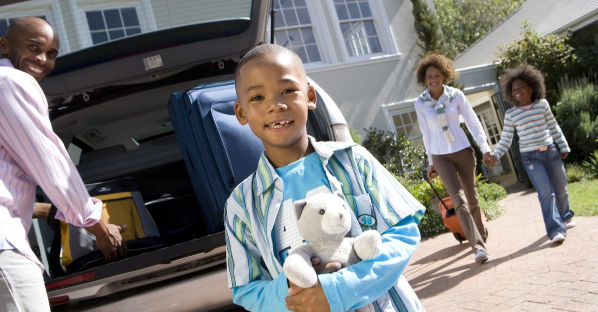 A family packs their car and prepares to leave on a trip as a little boy holding a Teddy bear looks into the camera