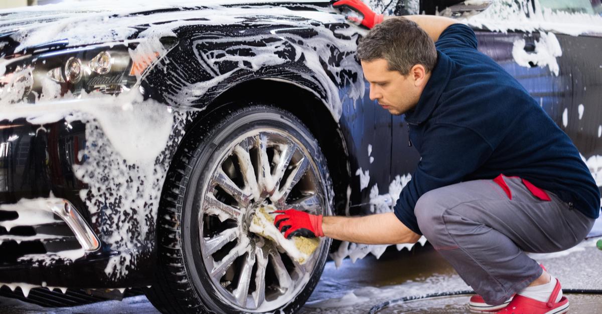 A car wash employee scrubs the tires of a car