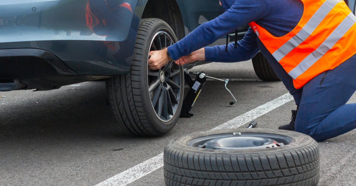 A roadside assistance service worker changes a tire at the side of the road
