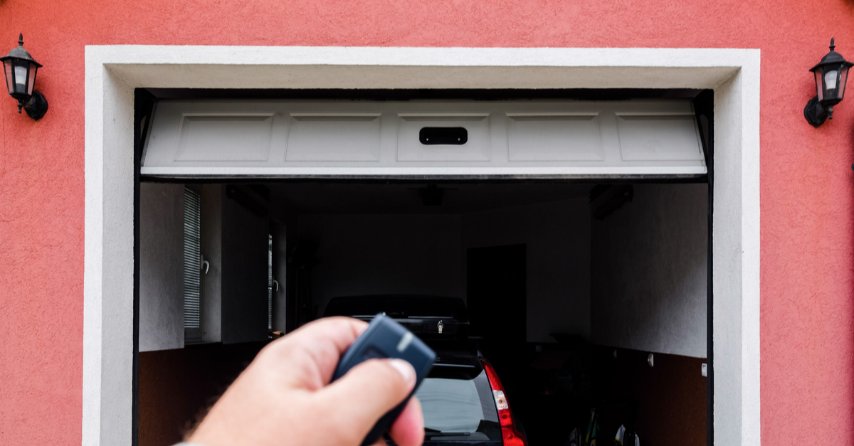 A car is in a garage and a person's hand can be seen with the garage door remote as the door goes down
