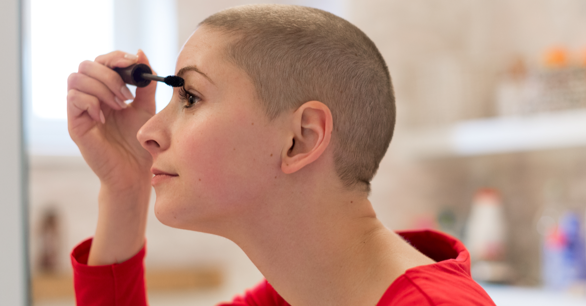 A woman recovering from cancer applies some makeup