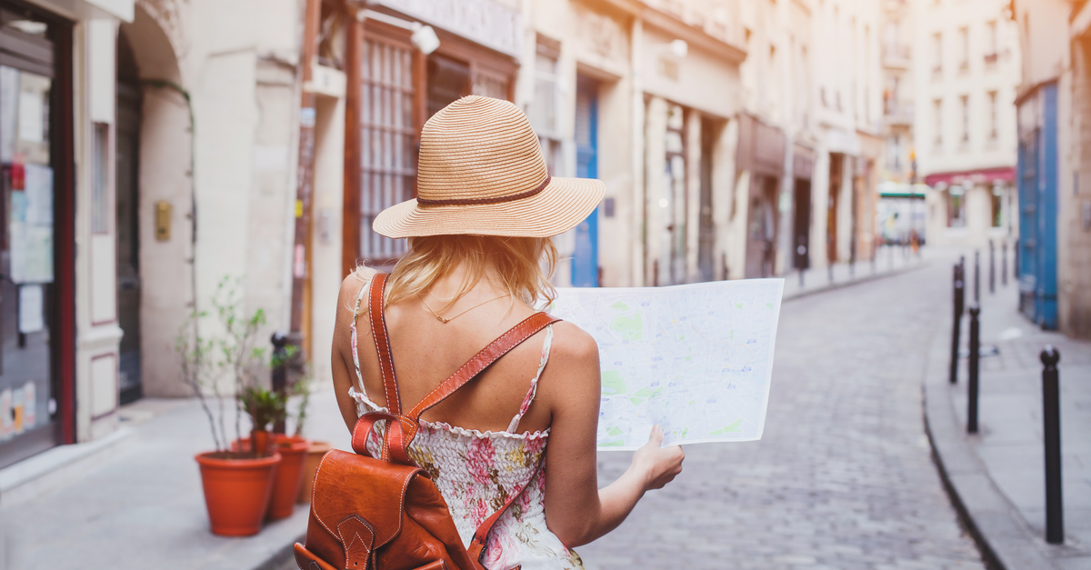 A woman walks on a small road in a European town as she holds a map
