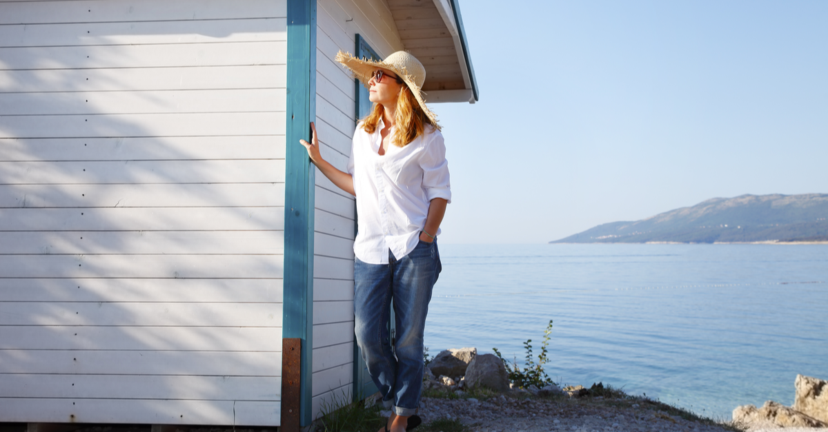 A woman is pictured by her coastal home