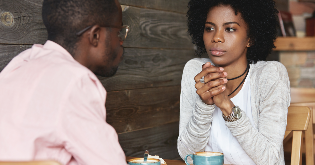 A man and woman are seen chatting in a coffee shop and discussing their financial goals
