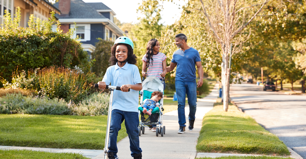 A couple and their two young children go for a walk in their new neighborhood after moving in.