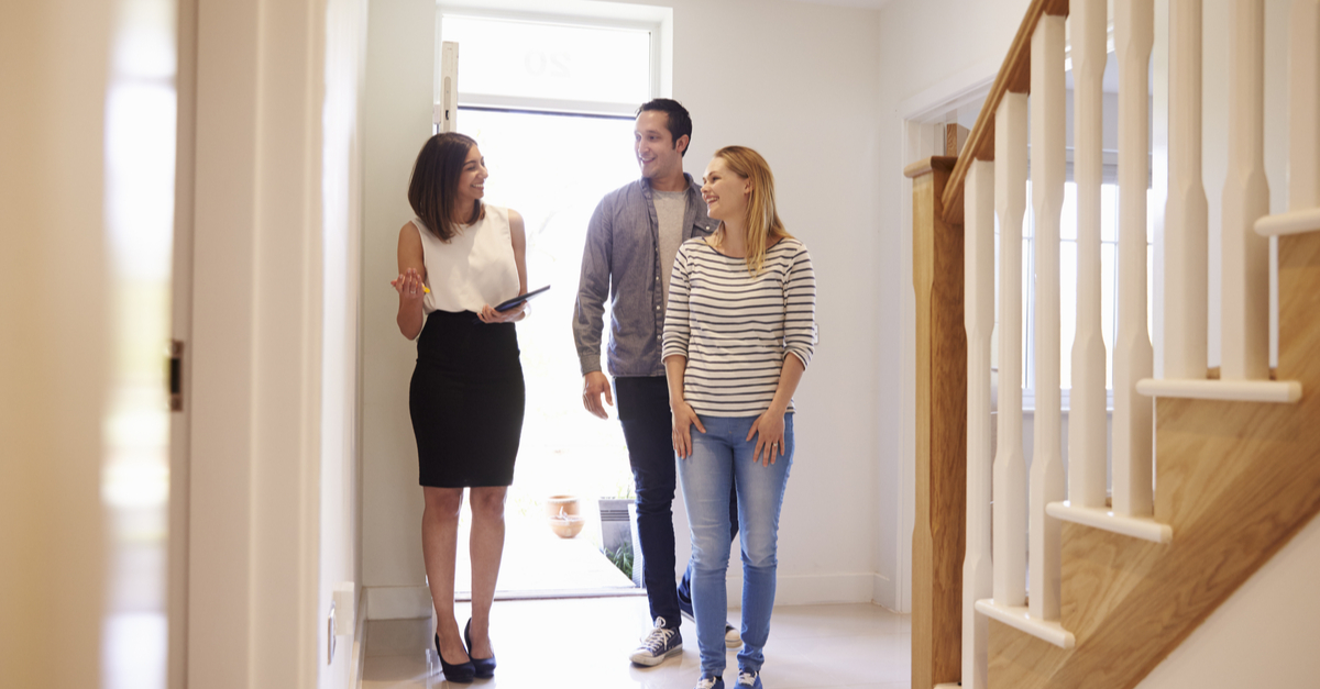 A real estate agent shows a house to a couple.