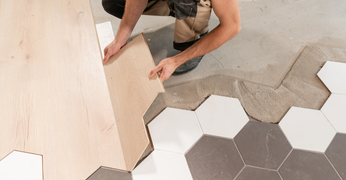 A man adds new tile flooring to a bathroom