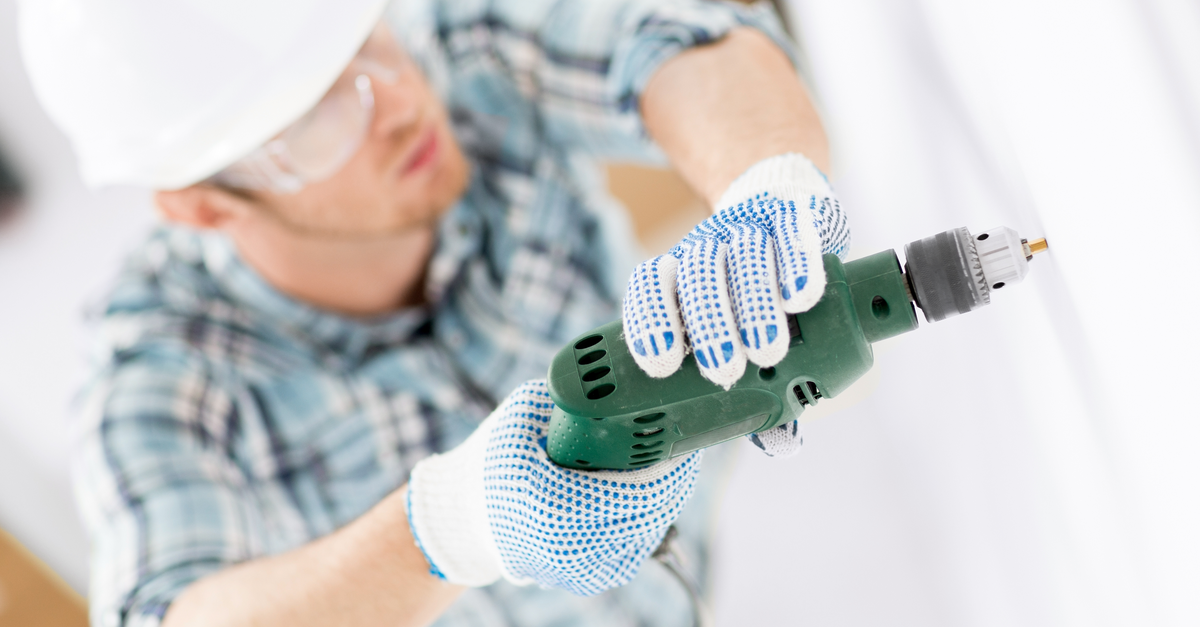 A subcontractor works on a home renovation while using a drill