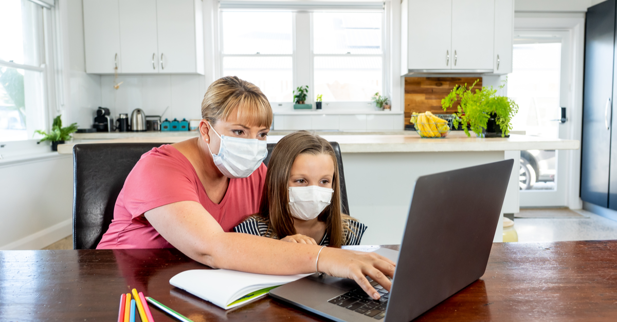 A tutor wears a mask as she helps a student in her home.