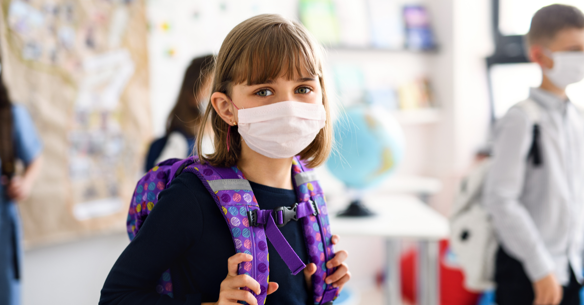 A girl wearing a backpack is seen in a classroom wearing a mask