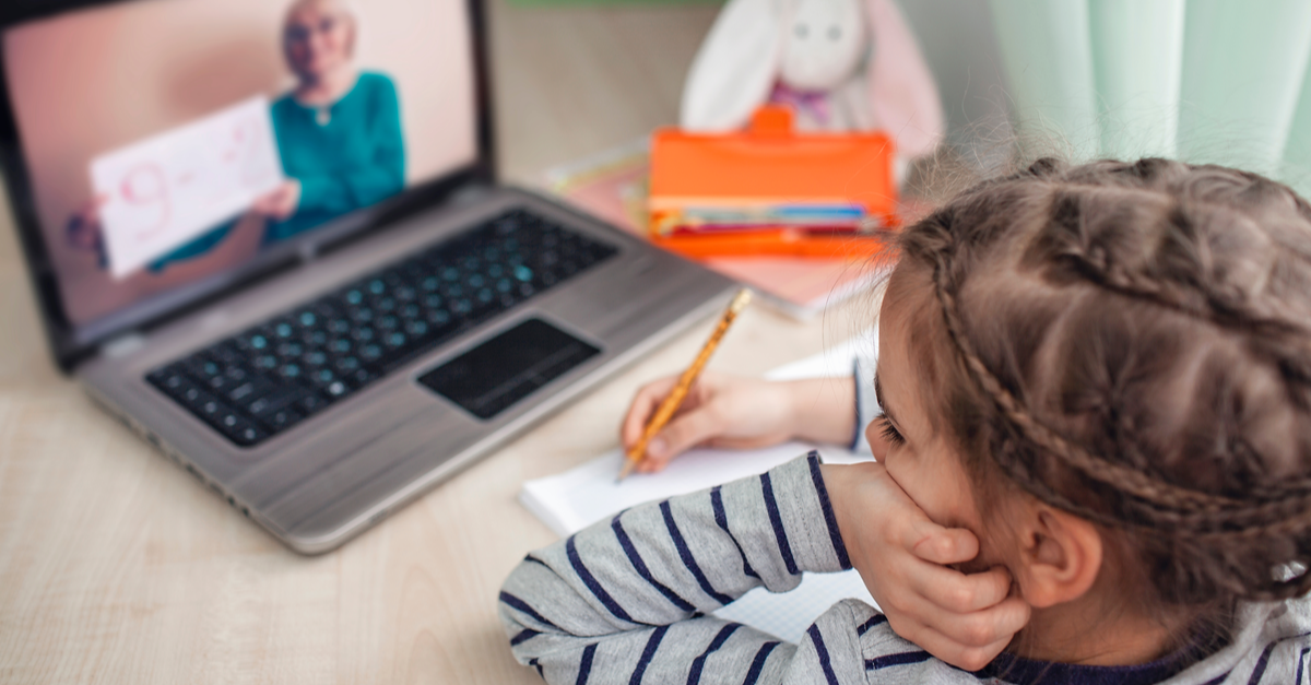 A young girl watches her teacher online as she attends virtual school