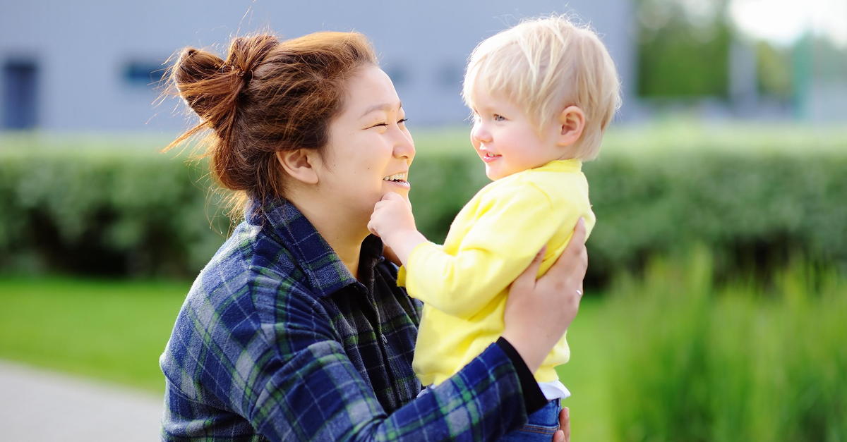 An au pair gives a toddler a hug as she smiles