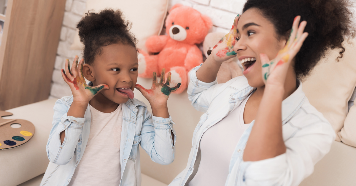 A babysitter and a young girl enjoy joking around