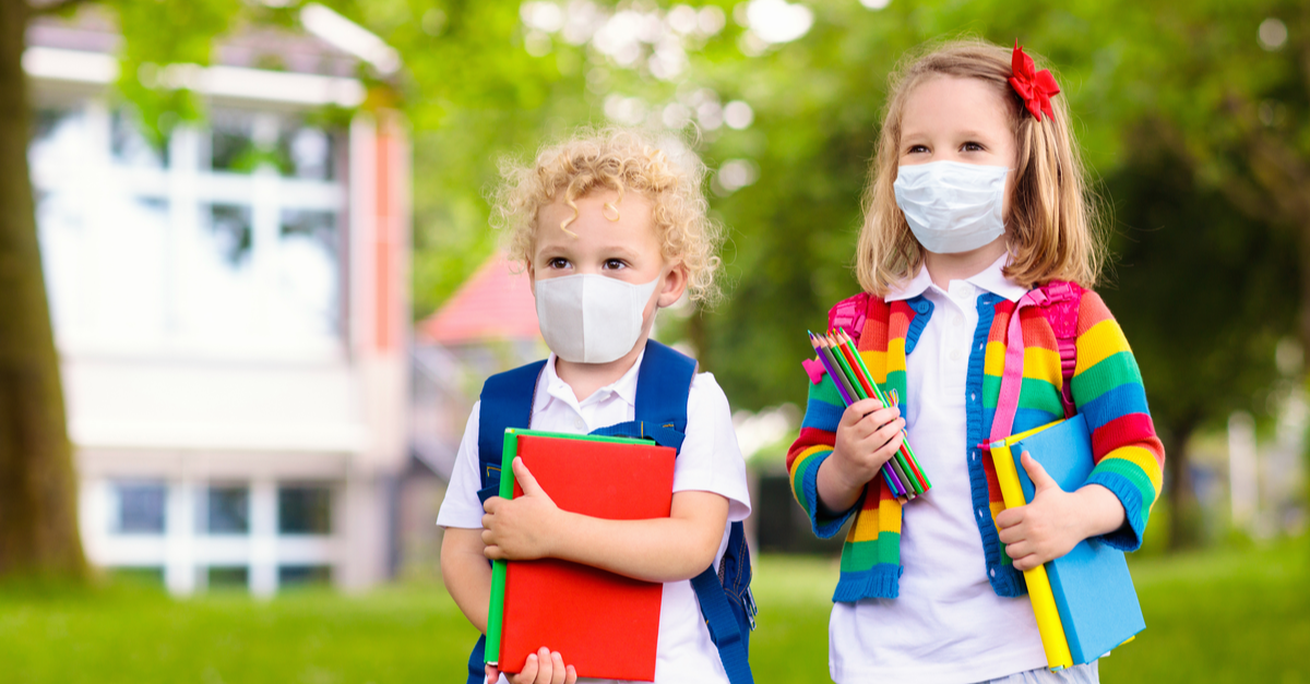 Two children are ready for school holding school supplies and wearing masks