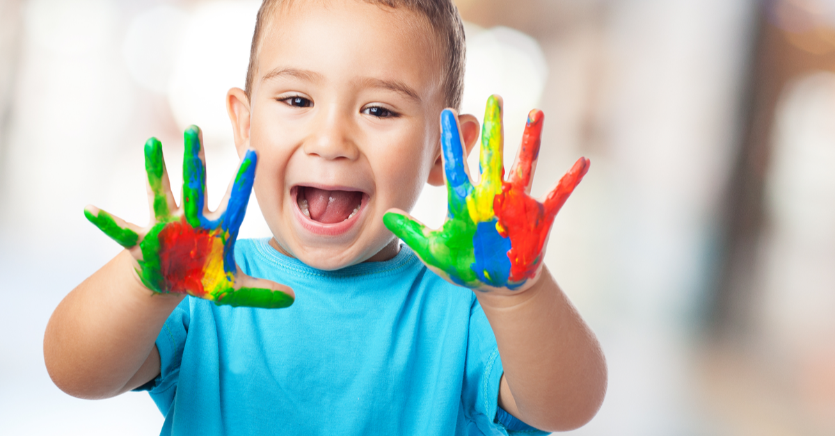 A preschool child shows his hands with paint on them