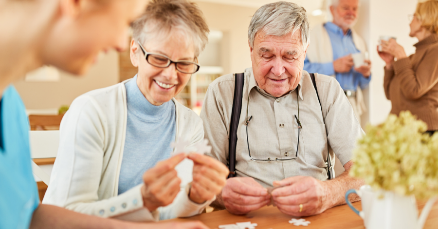 Seniors enjoy a game of cards at adult day care