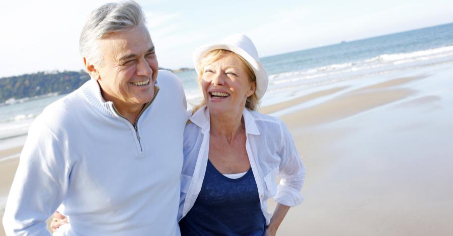 A senior couple enjoys a walk on the beach