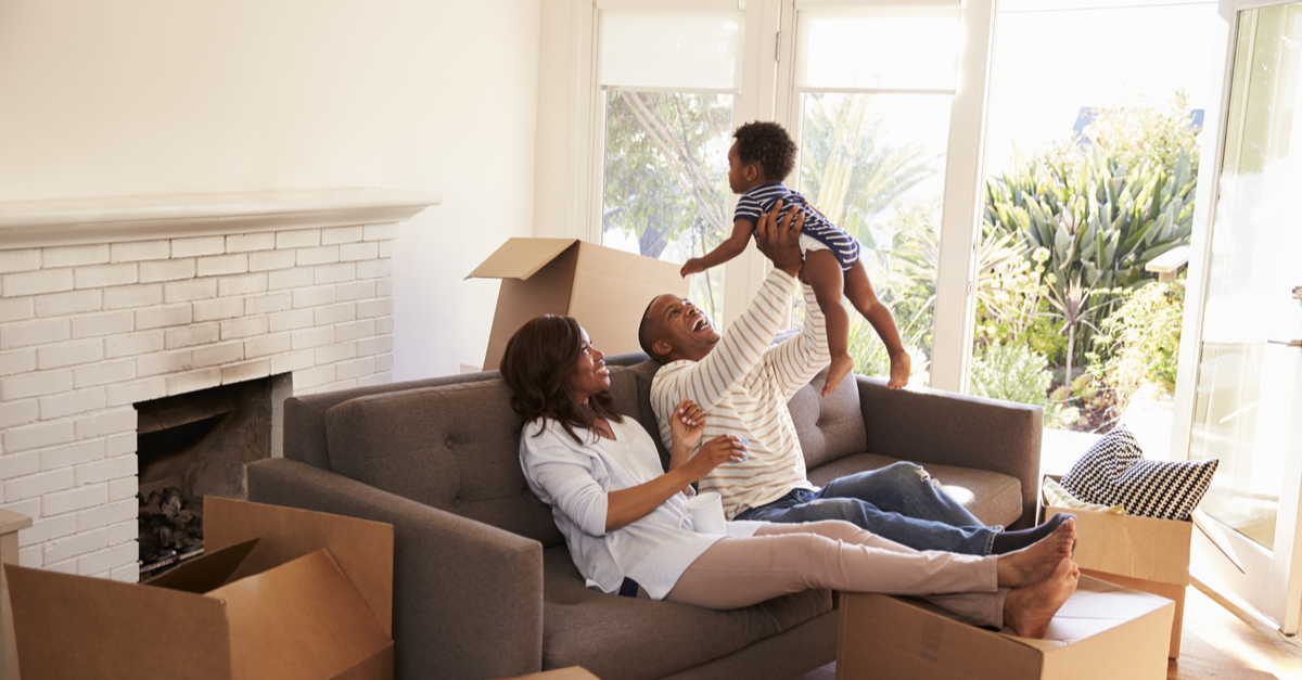 A couple relax in a living room surrounding by boxes as they play with their baby son
