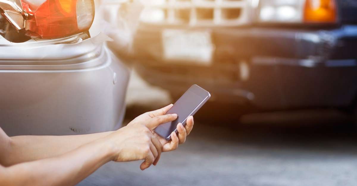 A person uses their cell phone after a car accident to document the damage