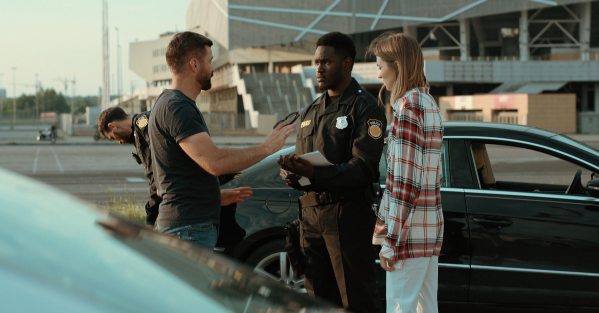 A police officer speaks with two drivers after a car accident