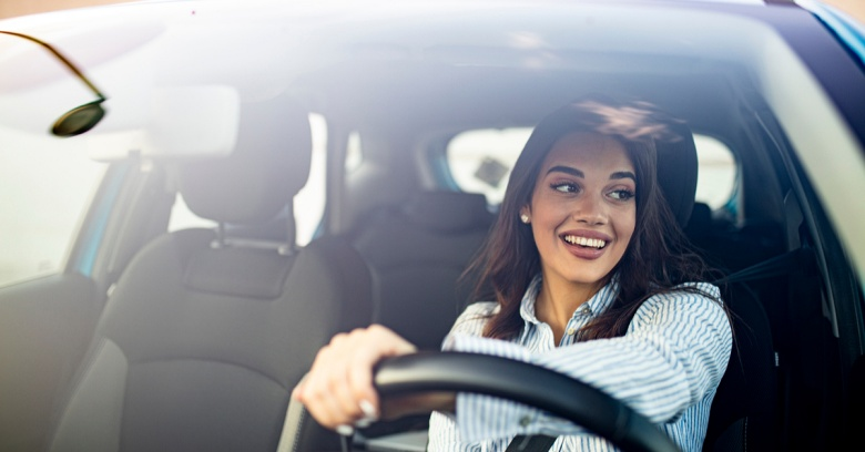 A smiling young businesswoman is inside her car with no passenger driving to work.