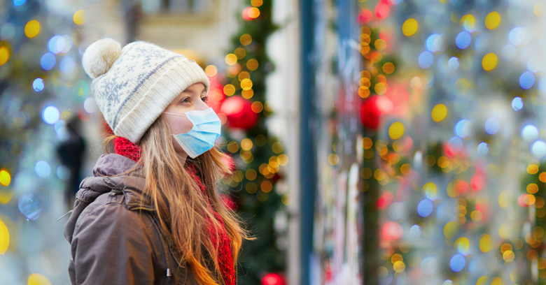 A woman wearing a mask enjoys looking at window displays during the holidays
