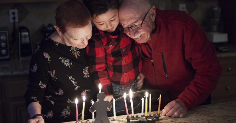 Grandparents light the Menorah candles with their grandchild on Hanukkah