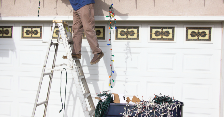 A man is precariously perched on a ladder as he hangs holiday lights