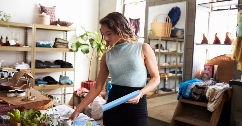 A woman is shown arranging items in a small, local boutique