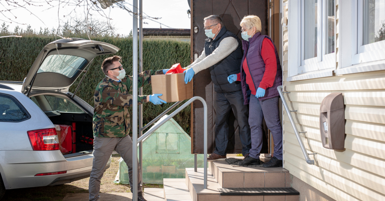 A volunteer delivers groceries to an older couple