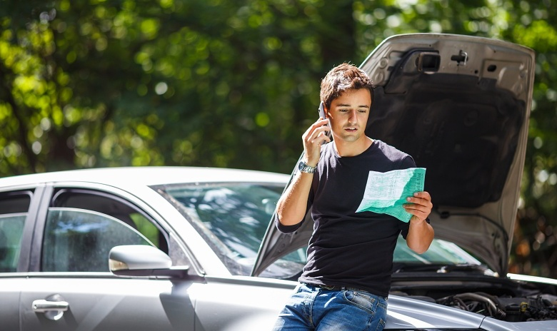 A young man calls his insurance company after his car breaks down.