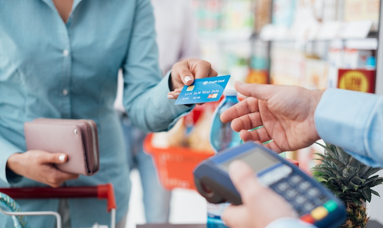 A woman pays by credit card at the grocery store.