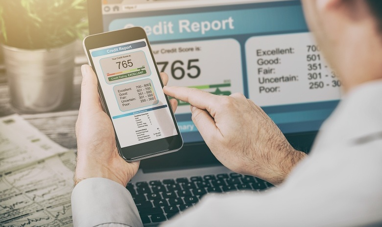 A man examines his credit report using his laptop and smartphone.