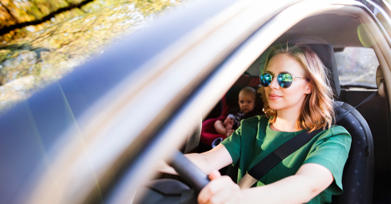 A woman drives her car with her baby in the backseat