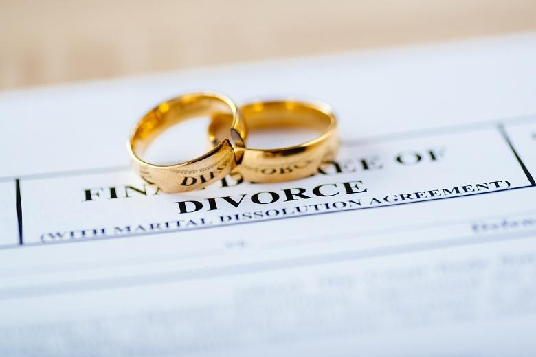 Two broken wedding rings sit on top of divorce paperwork.