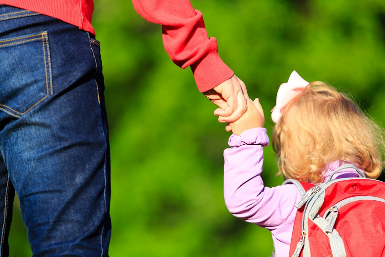 A mother holds her daughter's hand as they walk outdoors.